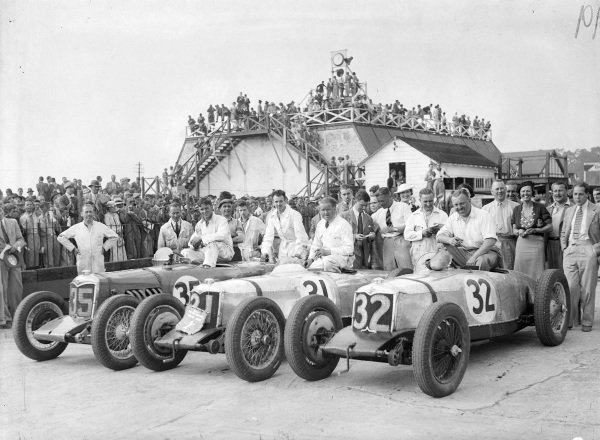 Edgar Maclure, 2nd position, Freddie Dixon, 1st position, and Cyril Paul, 3rd position, sit on their Rileys after the race.