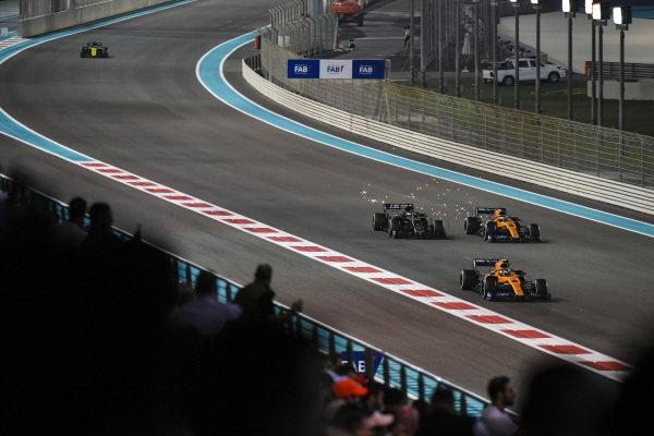 Lando Norris, McLaren MCL34, leads Carlos Sainz Jr., McLaren MCL34, Romain Grosjean, Haas VF-19, and Daniel Ricciardo, Renault R.S.19