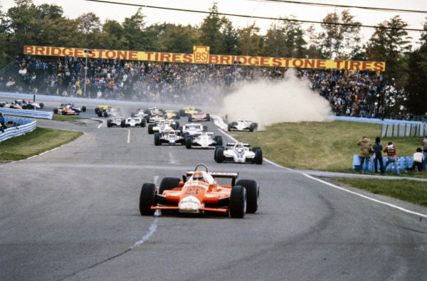 Bruno Giacomelli, Alfa Romeo 179, leads Nelson Piquet, Brabham BT49 Ford, Carlos Reutemann, Williams FW07B Ford, and Elio de Angelis, Lotus 81 Ford, at the start. Further back, Alan Jones, Williams FW07B Ford, runs off the road at the first corner.
