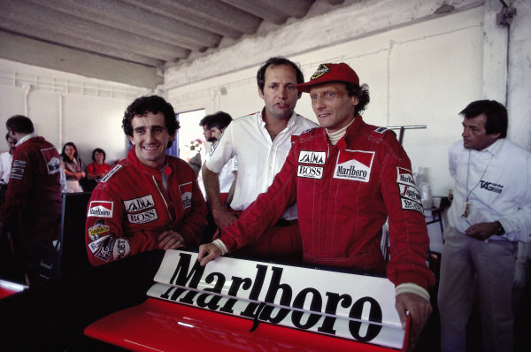Alain Prost, Ron Dennis and Niki Lauda in the McLaren garage with Hans Mezger behind.