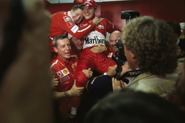 Michael Schumacher celebrating his fourth successive championship and sixth overall with the Ferrari team including Jean Todt.