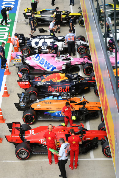 The cars of Charles Leclerc, Ferrari SF1000, Lando Norris, McLaren MCL35, Max Verstappen, Red Bull Racing RB16, Nico Hulkenberg, Racing Point RP20, Pierre Gasly, AlphaTauri AT01, and Daniel Ricciardo, Renault R.S.20, in Parc Ferme after Qualifying, with scrutineers and engineers