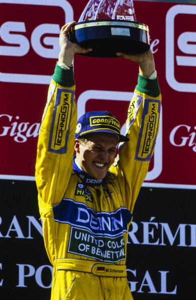 Michael Schumacher, 1st position, lifts his winner's trophy on the podium.
