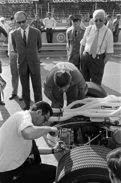 Enzo Ferrari looks over work being carried out Chris Amon's Ferrari 312 in the pit lane by engineer Mauro Forghieri.