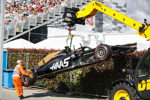 The Romain Grosjean Haas VF-19 is removed by a crane