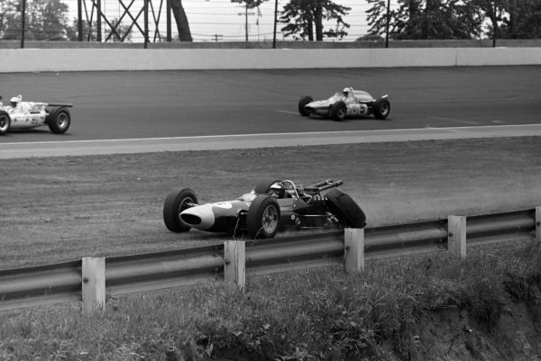 Jim Clark, Lotus 34 Ford, retires from the race with a suspension failure. Don Branson, Bob Wilke, Watson Offenhauser, is in the background.