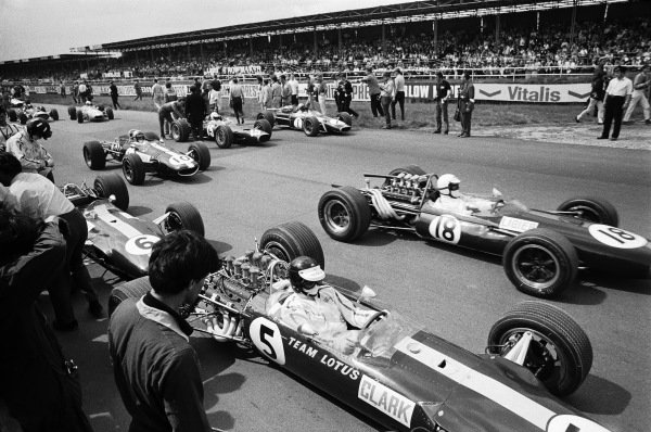 Jim Clark, Lotus 49 Ford, on the grid, with team mate Graham Hill behind, as Guy Ligier, Brabham BT20 Repco, drives past.