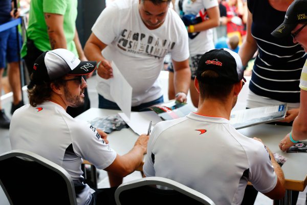 Hockenheim, Germany. Saturday 30 July 2016. Jenson Button, McLaren, and Fernando Alonso, McLaren, sign autographs for fans. World Copyright: Andy Hone/LAT Photographic ref: Digital Image _ONY7811
