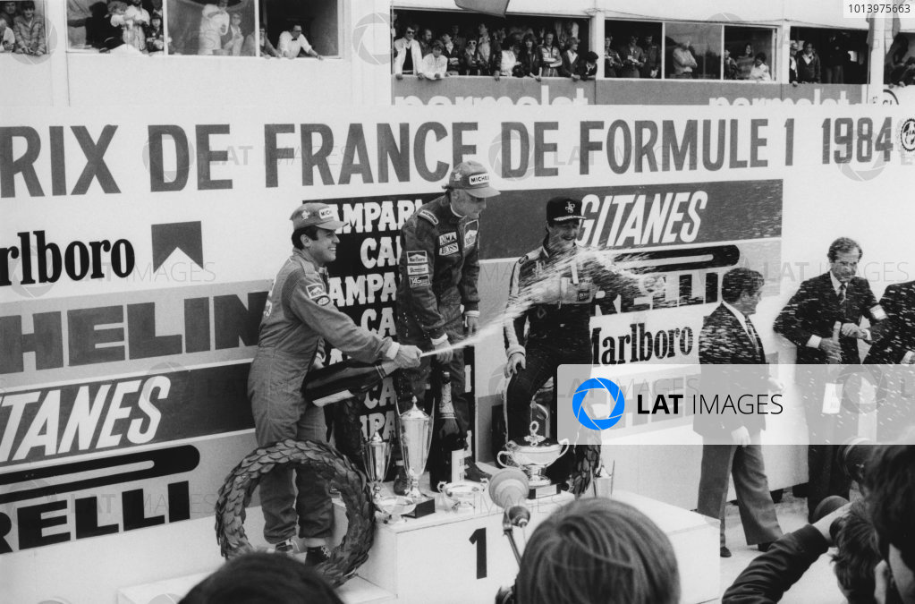 Dijon-Prenois, France 18th - 20th May 1984. Niki Lauda (McLaren MP4/2-TAG Porsche), 1st position with Patrick Tambay (Renault RE50) 2nd position and Nigel Mansell (Lotus 95T-Renault), 3rd position on the podium, portrait. World Copyright: LAT Photographic. Ref: B/W Print.