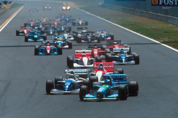 Tanaka International, Aida, Japan.15-17 April 1994.Michael Schumacher (Benetton B194 Ford) leads Ayrton Senna (Williams FW16 Renault), Mika Hakkinen, Martin Brundle (both McLaren MP4/9 Peugeot's) and Damon Hill (Williams FW16 Renault) at the start.Ref-94 PAC 15.World Copyright - LAT Photographic