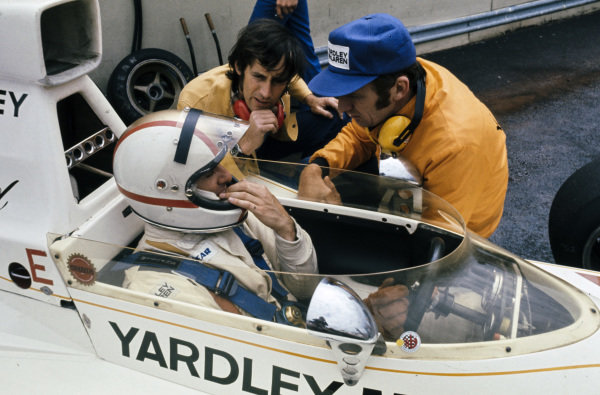 Mike Hailwood, McLaren M23 Ford talks to engineers in the pitlane.