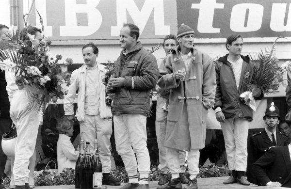 Bruce McLaren and Chris Amon, 1st position, flank Denny Hulme and Ken Miles, 2nd position, and Colin Davis and Jo Siffert, 1st position P2.0 class, on the podium.