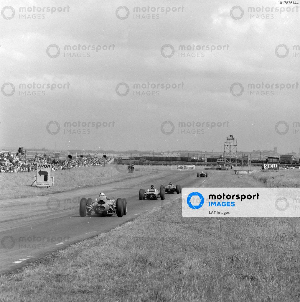 Graham Hill, BRM P57, leads Dan Gurney, Porsche 804, and Jack Brabham, Lotus 24 Climax.