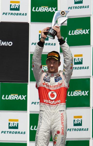 Interlagos, Sao Paulo, Brazil. 27th November 2011. Jenson Button, McLaren MP4-26 Mercedes, 3rd position, lifts his trophy. Portrait. Podium.  World Copyright: Steve Etherington/LAT Photographic ref: Digital Image SNE28328