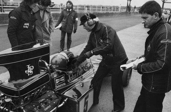 Silverstone, England. 12-14 July 1973.Ronnie Peterson (Lotus 72EFord), 2nd position, in the pits with team boss Colin Chapman as designer, Ralph Bellamy looks on, portrait.World Copyright: LAT PhotographicRef: B/W Print.