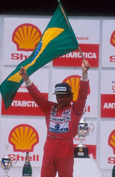 1991 Brazilian Grand Prix.Interlagos, Sao Paulo, Brazil.22-24 March 1991.Ayrton Senna (McLaren Honda) celebrates 1st position on the podium.Ref-91 BRA 09.World Copyright - LAT Photographic