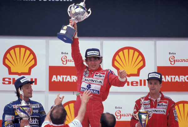 Riccardo Patrese, 2nd position, Ayrton Senna, 1st position, and Gerhard Berger, 3rd position, on the podium.