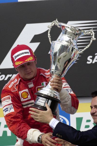 Race winner Kimi Räikkönen receives his trophy on the podium.