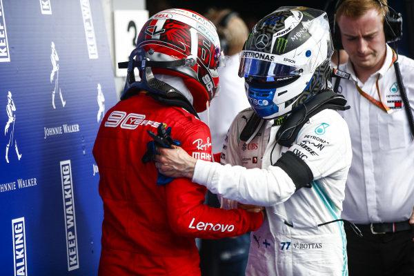 Charles Leclerc, Ferrari, celebrates in victory in parc ferme with Valtteri Bottas, Mercedes AMG F1