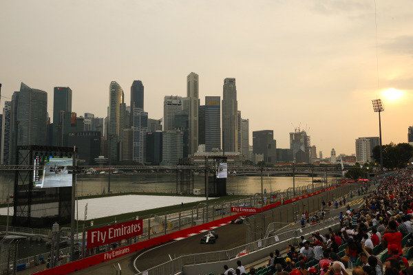 Fans watch Lance Stroll, Williams FW41, leads Kevin Magnussen, Haas F1 Team VF-18, in front of the Singapore skyline.