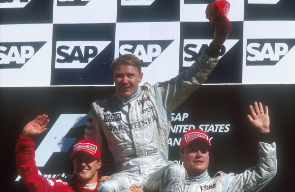 2001 United States Grand Prix.Indianapolis, Indiana, USA.28-30 September 2001.Mika Hakkkinen (McLaren Mercedes) 1st position is hoisted up onto the shoulders of Michael Schumacher (Ferrari) 2nd position and David Coulthard (McLaren Mercedes) 3rd position on the podium.Ref-01 USA 21.World Copyright - LAT Photographic