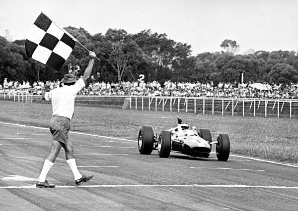 Warwick Farm, Australia. 13th February 1966. Jim Clark, Lotus 39-Climax, 1st position, takes the chequered flag, action. World Copyright: LAT Photographic.