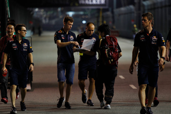 Marina Bay Circuit, Singapore. Thursday 17 September 2015. Daniil Kvyat, Red Bull Racing, signs autographs for fans, as he walks the track with his engineers. World Copyright: Sam Bloxham/LAT Photographic ref: Digital Image _G7C3255