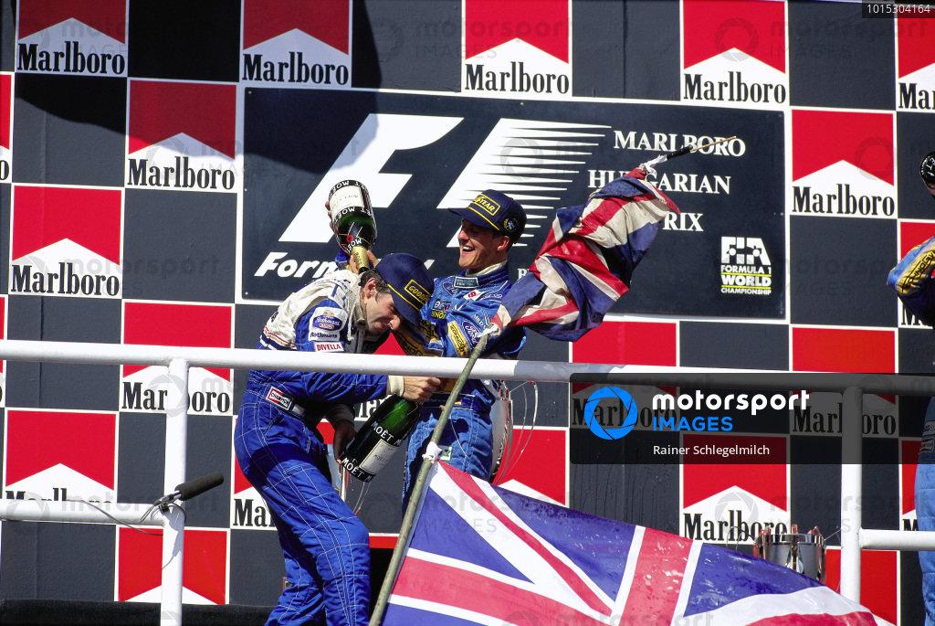 Winner Michael Schumacher celebrates on the podium with Damon Hill, 2nd position.