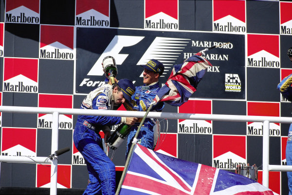 Winner Michael Schumacher celebrates on the podium with Damon Hill, 2nd position.