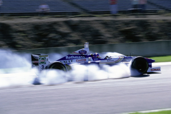 Jacques Villeneuve, Williams FW19 Renault, locks his front brakes.