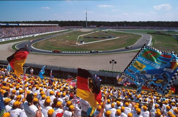 The huge crowd in the Hockenheim stadium cheer on the drivers.