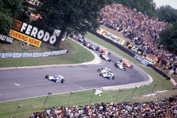 Brands Hatch, Great Britain. 11-13 July 1980. Didier Pironi leads Jacques Laffite (both Ligier JS11/15-Ford Cosworth), Alan Jones, Carlos Reutemann (both Williams FW07B-Ford Cosworth), Nelson Piquet (Brabham BT49-Ford Cosworth), Patrick Depailler, Bruno Giacomelli (both Alfa Romeo 179B), Derek Daly (Tyrrell 010-Ford Cosworth), Mario Andretti (Lotus 81-Ford Cosworth) and Jean-Pierre Jarier (Tyrrell 010-Ford Cosworth) out of Druids hairpin on lap one. World Copyright: LAT Photographic. Ref: 80GB33