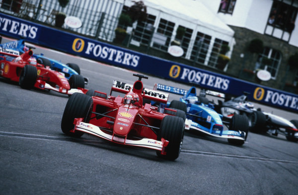 Michael Schumacher, Ferrari F2001, leads Giancarlo Fisichella, Benetton B201 Renault, Mika Häkkinen, McLaren MP4-16 Mercedes, and Rubens Barrichello, Ferrari F2001, round La Source at the start.