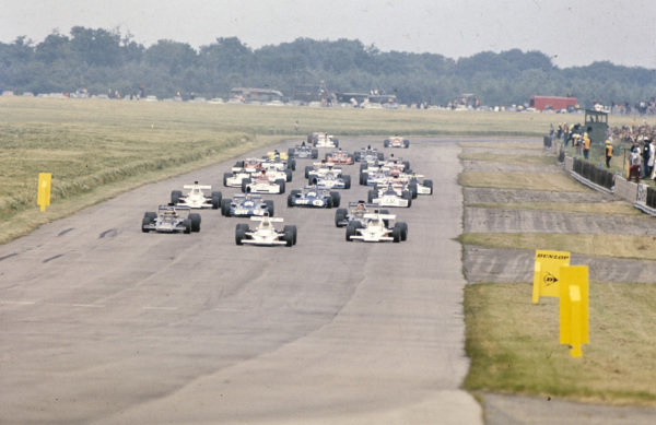 Denny Hulme, McLaren M23 Ford leads the field with Peter Revson, McLaren M23 Ford and Ronnie Peterson, Lotus 72E Ford behind.