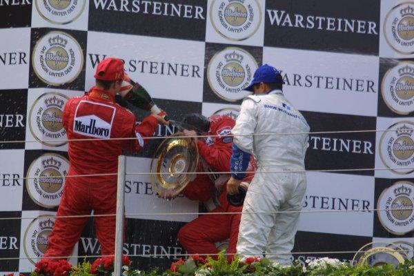 2001 European Grand Prix. RACENurburgring, Germany. 24th June 2001Race winner Michael Schumacher, Ferrari F2001, and Juan Pablo Montoya, BMW Williams FW23 (2nd) spray Nigel Stepney with champagne. Podium.World Copyright - LAT Photographicref: 8 9 MB Digital File Only