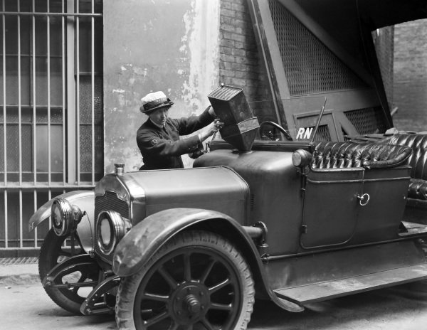 A member of the Women's Royal Naval Service refuels a car during her driver training at the WRNS Garage in Charing Cross.
