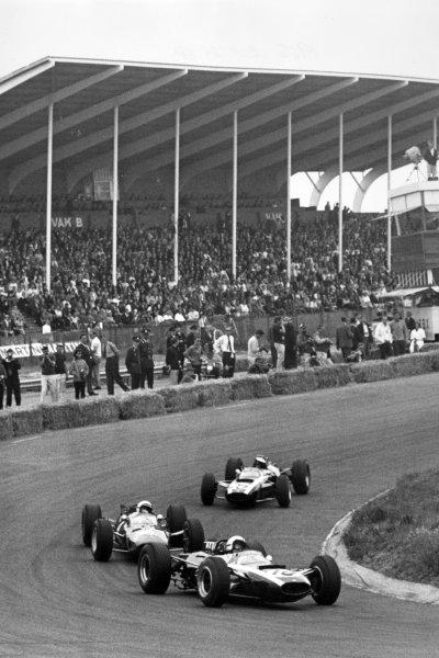 1965 Dutch Grand Prix.Zandvoort, Holland. 18 July 1965.Bruce McLaren, Cooper T77-Climax, retired, leads Lorenzo Bandini, Ferrari 158, 9th position, and Jochen Rindt, Cooper T77-Climax, retired, action.World Copyright: LAT PhotographicRef: Motor b&w print