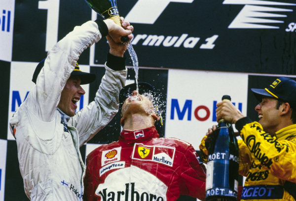 Mika Häkkinen, 3rd position, Michael Schumacher, 1st position, and Giancarlo Fisichella, 2nd position, celebrate with champagne on the podium. Häkkinen would later be disqualified for a fuel irregularity.
