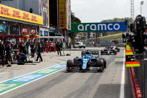 Fernando Alonso, Alpine A521, leads Pierre Gasly, AlphaTauri AT02, ion the pit lane