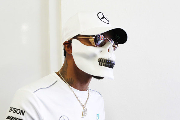 Lewis Hamilton, Mercedes AMG F1, wears a skull mask during an autograph signing