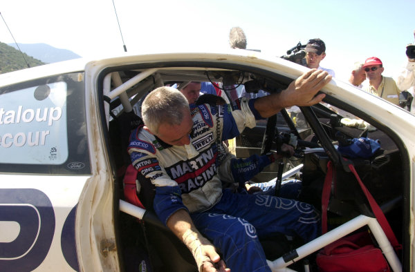 2001 World Rally Championship.Acropolis Rally June 14-17, 2001.Francois Delecour climbs out of the co-drivers seat because of his injured wrist is too painful for him to drive the liaison section to the regroup during leg 2.Photo: Ralph Hardwick/LAT