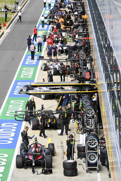 The F2 teams prepare their cars for the race in the pit lane prior to the start