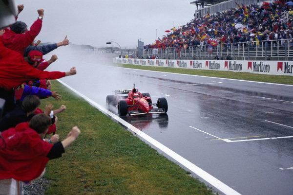 The Ferrari team celebrate Michael Schumacher's victory in the Ferrari F310.