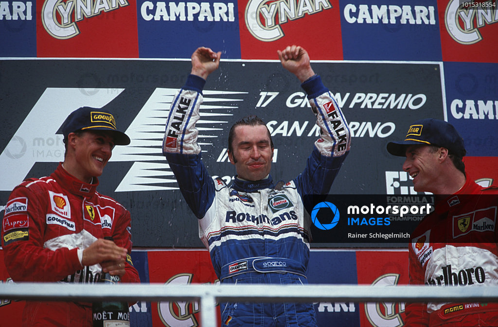 Michael Schumacher, 2nd position, Heinz-Harald Frentzen, 1st position, and Eddie Irvine, 3rd position, celebrate on the podium.