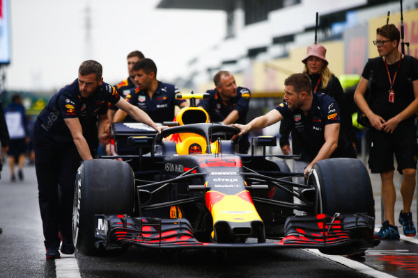 Red Bull Racing mechanics push the car of Max Verstappen, Red Bull Racing RB14, in the pit lane.