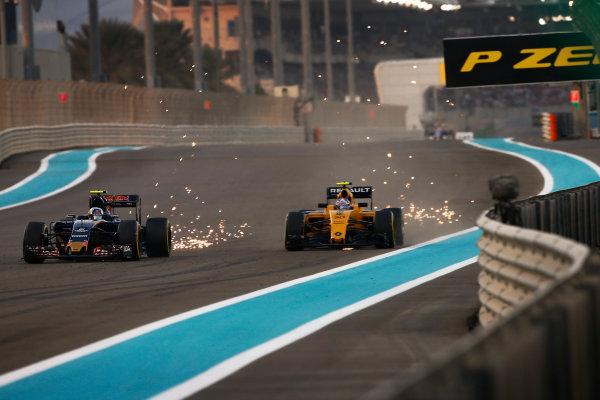 Yas Marina Circuit, Abu Dhabi, United Arab Emirates. Sunday 27 November 2016. Carlos Sainz Jr, Toro Rosso STR11 Ferrari, battles with Jolyon Palmer, Renault RE16. World Copyright: Andy Hone/LAT Photographic ref: Digital Image _ONZ0324