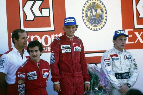 1984 Portuguese Grand Prix. Estoril, Portugal. 21st October 1984. Ron Dennis, Alain Prost (McLaren MP4/2-TAG Porsche) 1st position, Niki Lauda (McLaren MP4/2-TAG Porsche) 2nd position and World Champion, Ayrton Senna (Toleman TG184-Hart) 3rd position, on the podium.  Ref: 84POR12. World Copyright: LAT Photographic