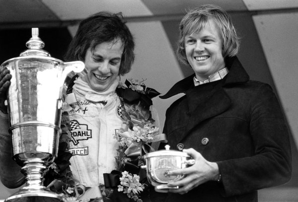 Motor Show 200. Rd 14.Brands Hatch, England. 21st October 1973.Tony Brise (March 733 - Ford), 1st position, recieves his winning trophies from Ronnie Peterson after winning the race and championship, podium, portrait. World Copyright: LAT Photographic.Ref:  5863 - 5-5A.