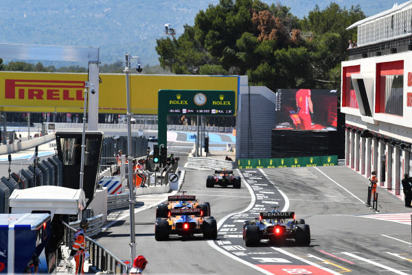 Pierre Gasly, Red Bull Racing RB15, Carlos Sainz Jr., McLaren MCL34, Lando Norris, McLaren MCL34, and Max Verstappen, Red Bull Racing RB15, leave the pits during Qualifying