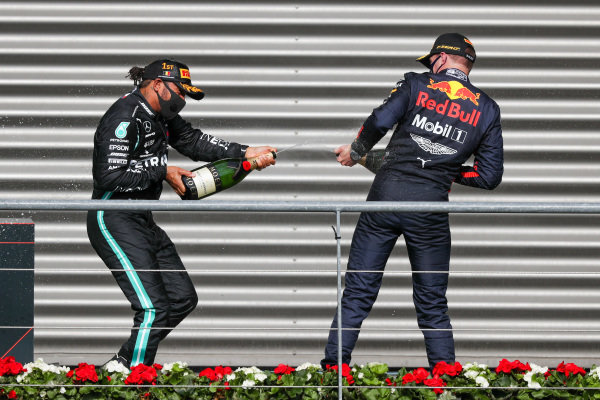 Lewis Hamilton, Mercedes-AMG Petronas F1, 1st position, and Max Verstappen, Red Bull Racing, 3rd position, spray Champagne on the podium